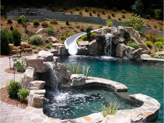 This Natural, Lagoon Style Poolscape Boasts A Curvaceous Custom Waterslide,  Cascading Waterfalls, Rock Grotto, And Custom Spa, Offering Endless Hours  Of ...